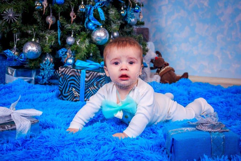 Um rapaz pequeno está sentando-se nos presentes sob a árvore Presentes do ano novo O menino sob a árvore foto de stock royalty free