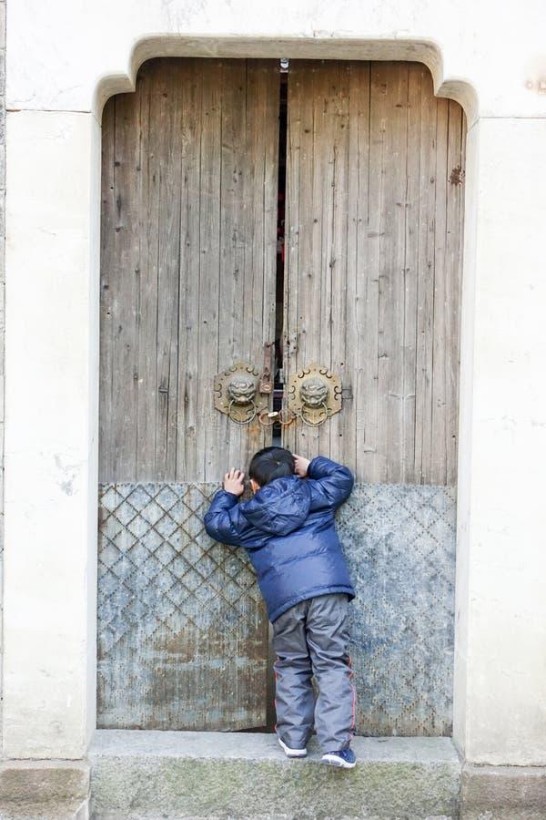 Um rapaz pequeno estava encontrando-se na frente da porta de madeira e olhado para dentro fotos de stock royalty free