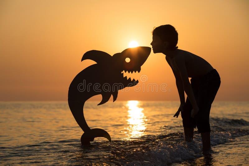 Um rapaz pequeno feliz que joga na praia no tempo do por do sol imagem de stock