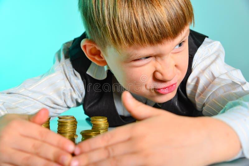 Um rapaz pequeno irritado e ávido esconde suas economias do dinheiro O conceito ávido e vicioso da riqueza estragou uma criança d fotografia de stock royalty free