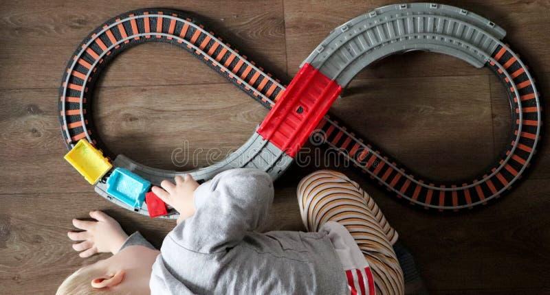 Um rapaz pequeno joga uma estrada de ferro das crianças A mamã está olhando seu filho de cima de A criança é fascinada pelo trem imagens de stock
