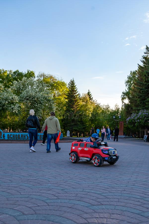 Um rapaz pequeno monta um carro elétrico vermelho ao andar com seus pais em um parque da cidade com as árvores verdes, rindo e so fotografia de stock royalty free
