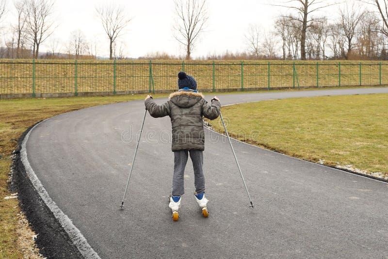 Um rapaz pequeno monta o esqui corta-mato do treinamento do verão com rolos em um relvado artificial vermelho Preparações para a  foto de stock royalty free
