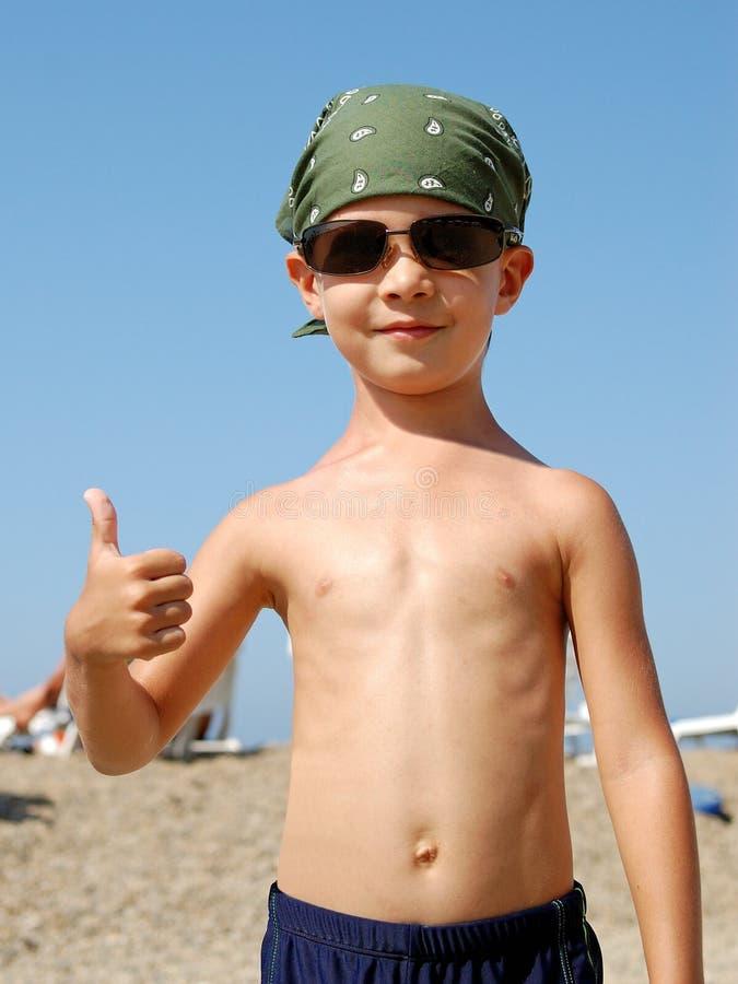 Um rapaz pequeno mostra ESTÁ BEM na praia fotos de stock royalty free