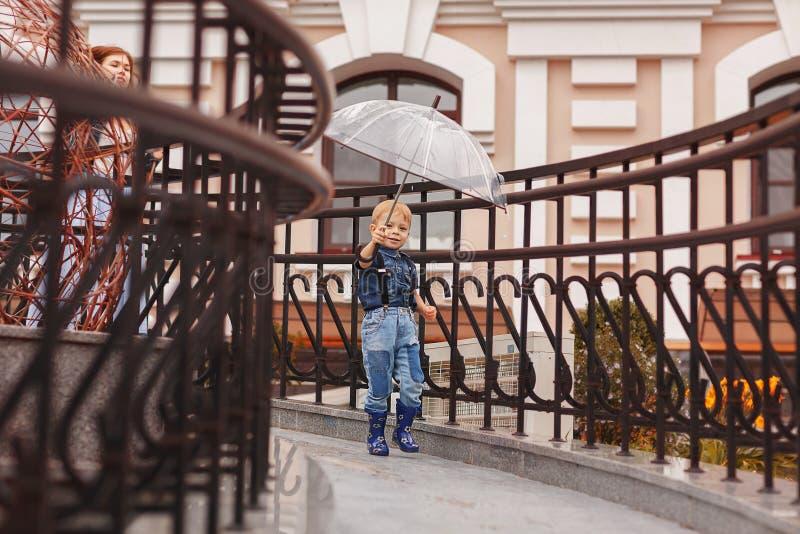 Um rapaz pequeno nas botas de borracha corre sob um guarda-chuva em um dia chuvoso foto de stock royalty free