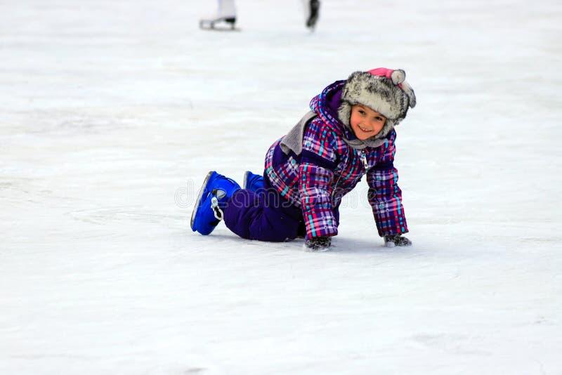 Um rapaz pequeno patina e cai no gelo nas crianças patina esporte ativo da família da pista, feriados de inverno, clube desportiv fotografia de stock royalty free