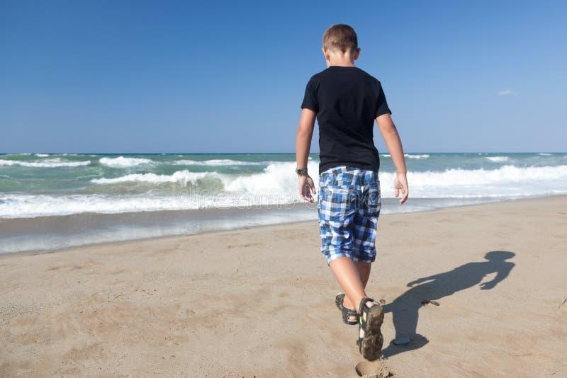 Um rapaz pequeno que anda sozinho na praia 1 imagem de stock royalty free