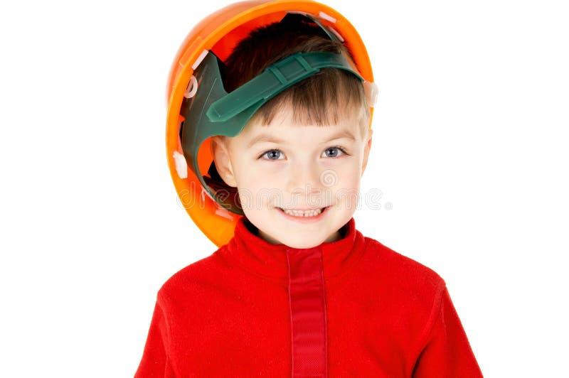 Um rapaz pequeno que está com um capacete imagem de stock