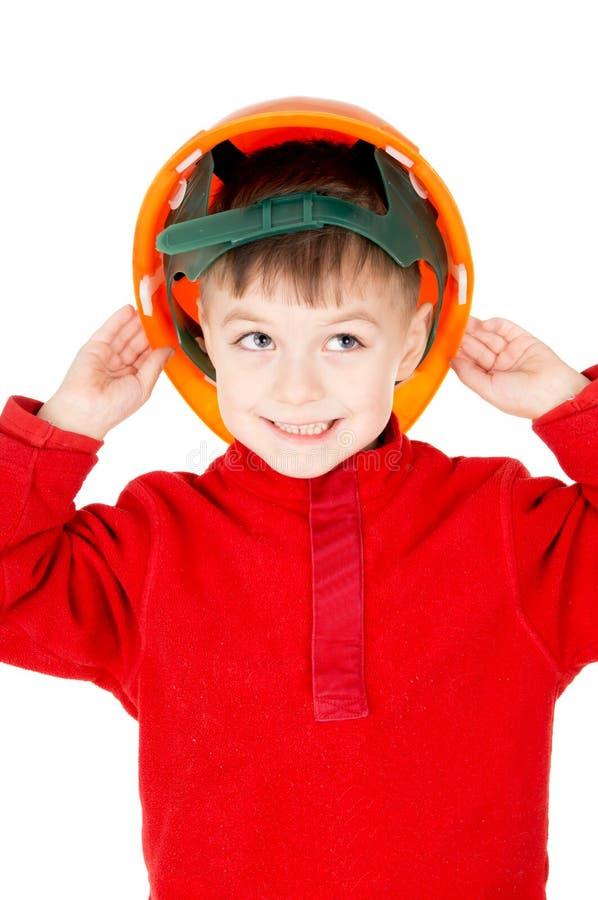 Um rapaz pequeno que está com um capacete imagens de stock