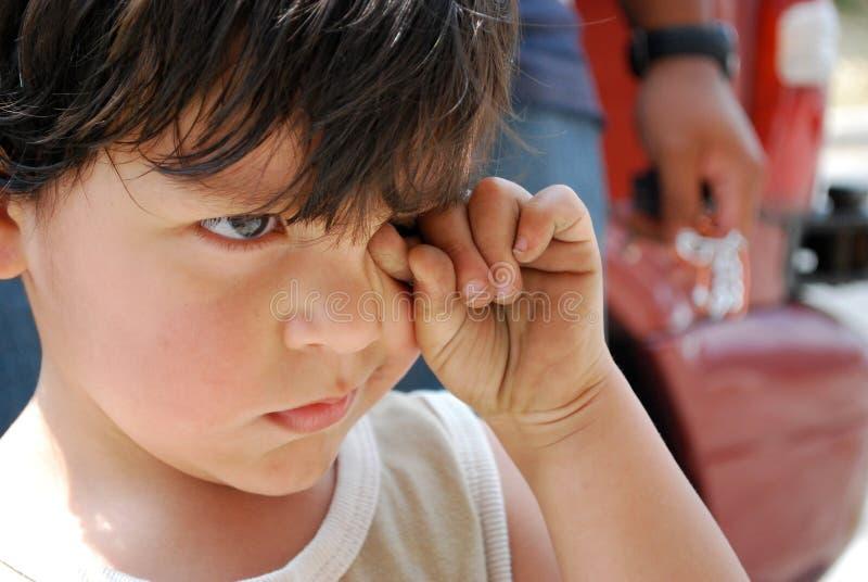 Um rapaz pequeno que fricciona triste seus olhos fotografia de stock