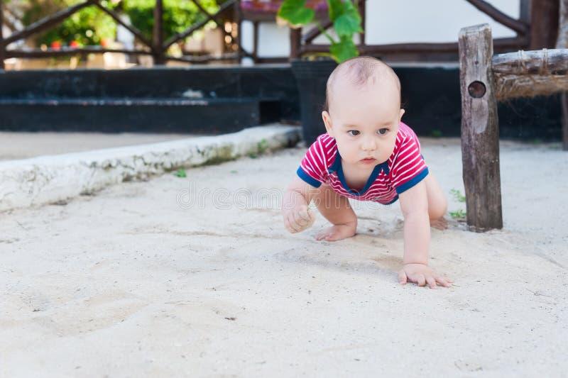 Um rapaz pequeno que joga em uma areia branca Criança com os brinquedos para o sa fotografia de stock