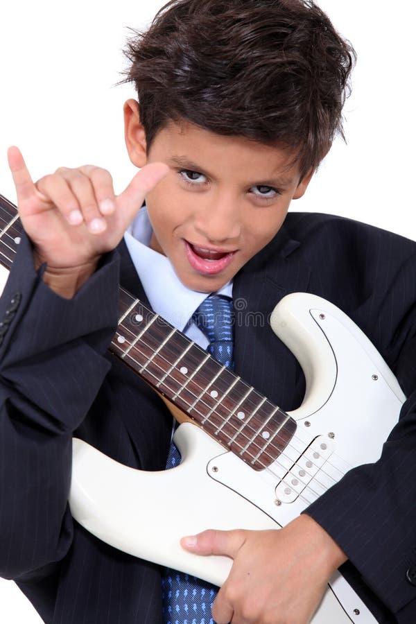 Um rapaz pequeno que joga a guitarra imagem de stock royalty free