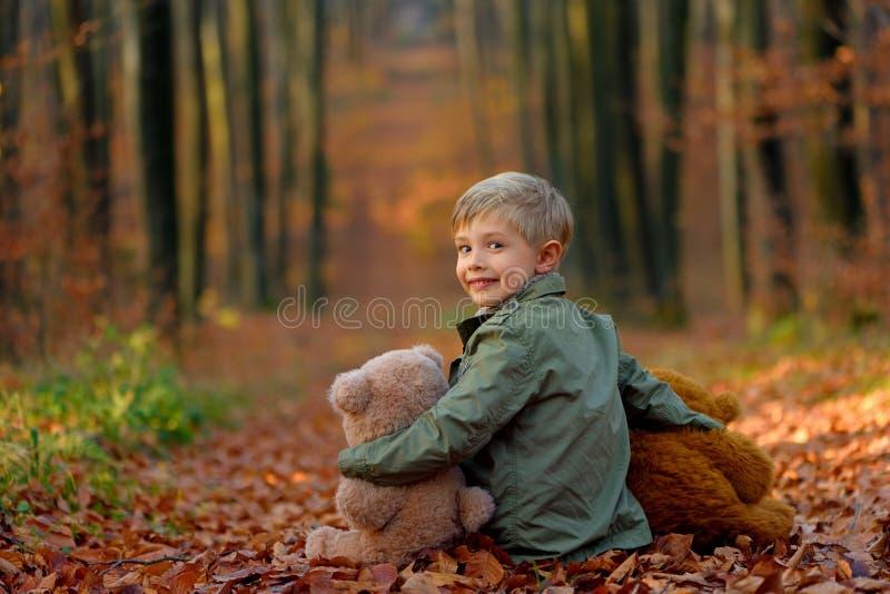 Um rapaz pequeno que joga no parque do outono fotos de stock