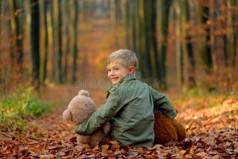 Um rapaz pequeno que joga no parque do outono foto de stock royalty free