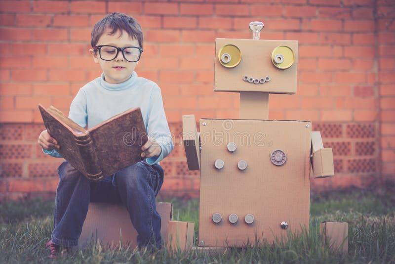 Um rapaz pequeno que lê ao robô das caixas de cartão fora foto de stock royalty free