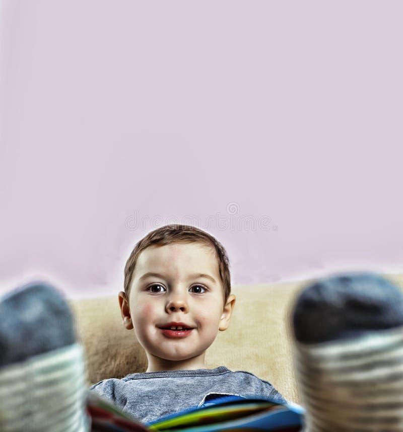 Um rapaz pequeno que lê um livro ao sentar-se no sofá em casa fotografia de stock