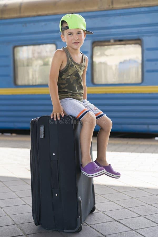 Um rapaz pequeno que situa em uma mala de viagem preta grande na estação Conceito do curso e da aventura Foto vertical imagem de stock royalty free