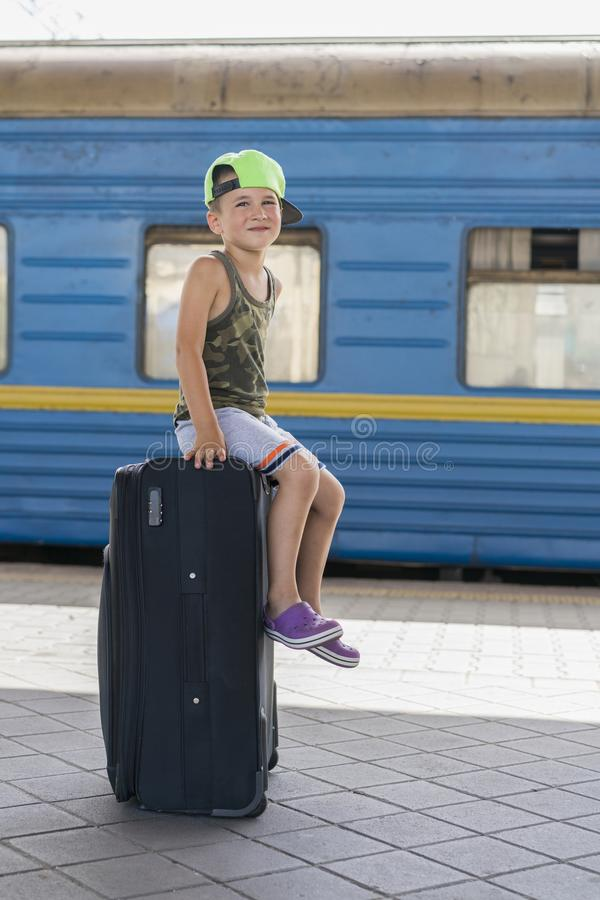 Um rapaz pequeno que situa em uma mala de viagem preta grande na estação Conceito do curso e da aventura Foto vertical imagens de stock