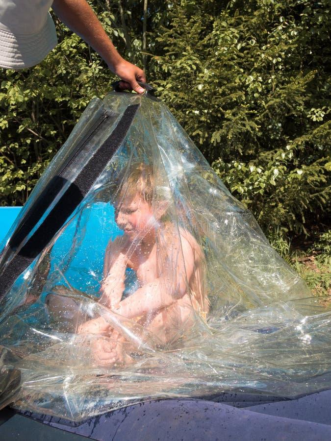 Um rapaz pequeno senta-se de pernas cruzadas dentro de uma tampa plástica transparente imagem de stock