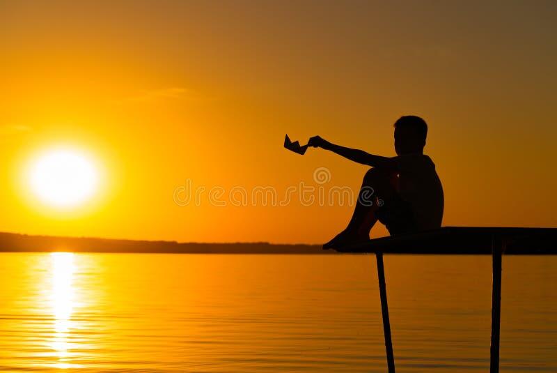 Um rapaz pequeno senta-se em uma ponte e guarda-se o navio do papel em sua mão no por do sol no rio Uma criança joga com próprio  imagens de stock