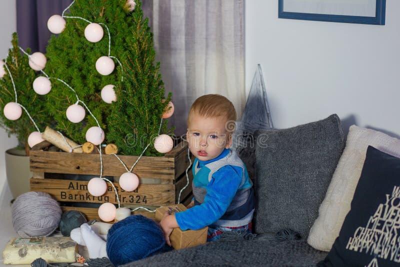 Um rapaz pequeno senta-se pela árvore de Natal em antecipação ao holid imagem de stock