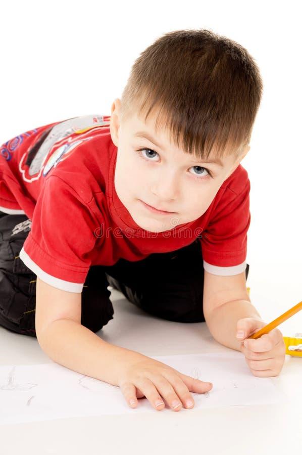 Um rapaz pequeno tira no papel imagem de stock