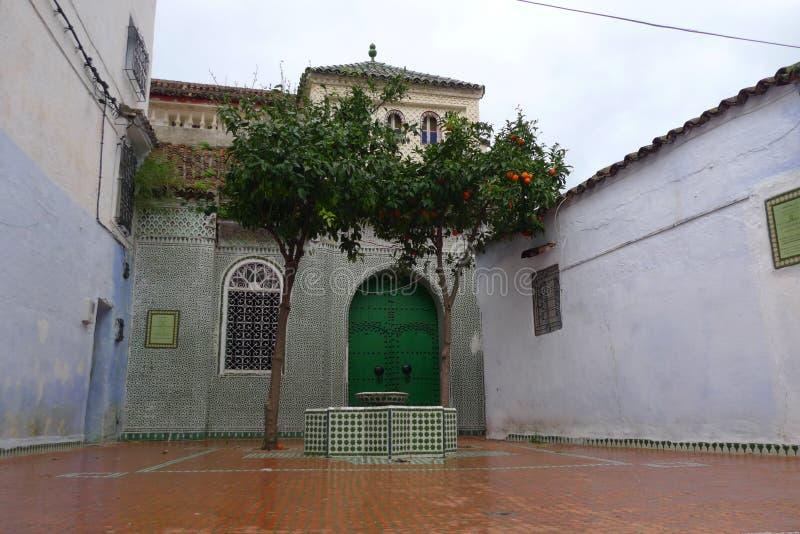 Um raro dia molhado em Marrocos, tomando a piscina de azulejos médios e a porta verde fotografia de stock