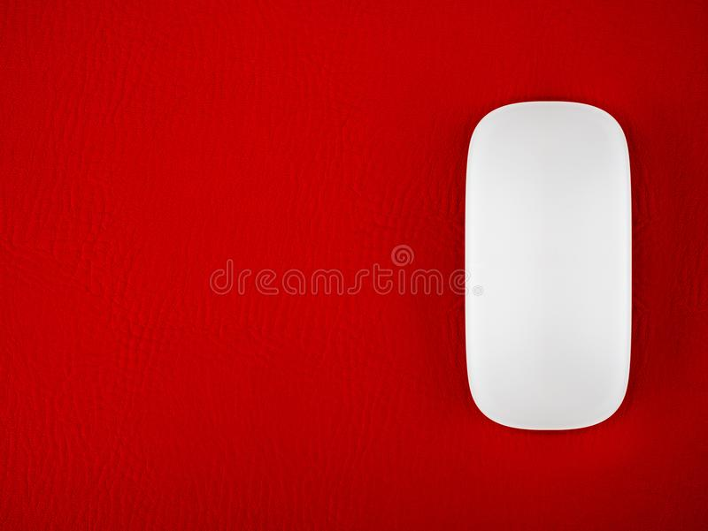 Um rato branco do computador em um fundo vermelho da textura do tapete do rato imagens de stock