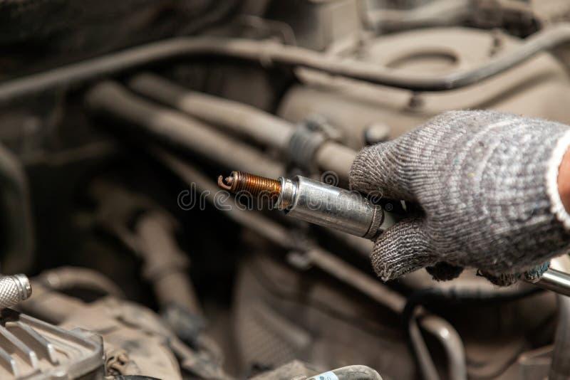 Um recruta repara um carro ao substituir as velas de ignição ao guardar um delas à disposição com uma luva ao desaparafusá-las fotografia de stock royalty free