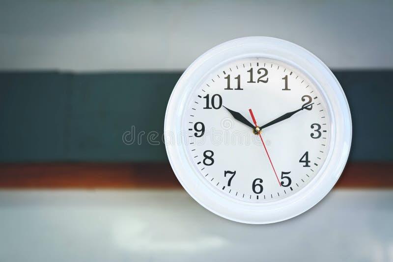 Um relógio na parede com espaço da cópia no borrão fotografia de stock