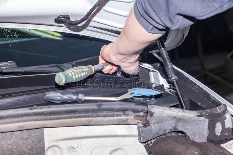 Um reparador do carro desaparafusa partes com uma chave com um punho verde no compartimento de motor em um reparo do veículo imagem de stock royalty free