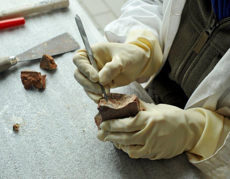 Um restaurador das belas artes que limpa a antiguidade cerâmica com o escalpelo imagem de stock royalty free