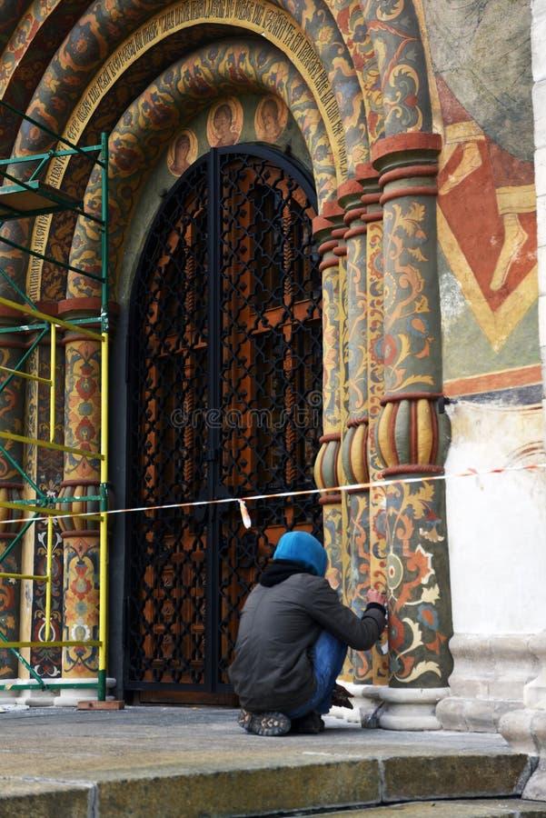 Um restaurador no trabalho, fachada da igreja de Dormition do Kremlin de Moscou Local do património mundial do Unesco imagens de stock