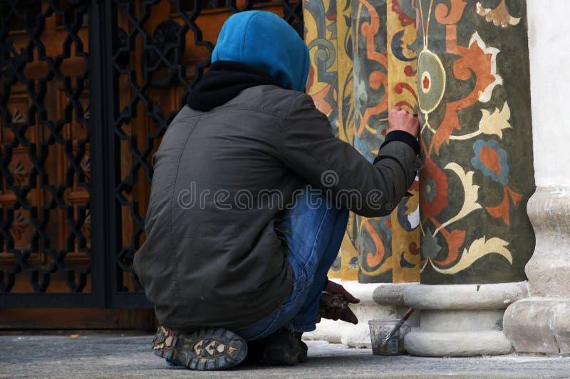 Um restaurador no trabalho, fachada da igreja de Dormition do Kremlin de Moscou Local do património mundial do Unesco foto de stock
