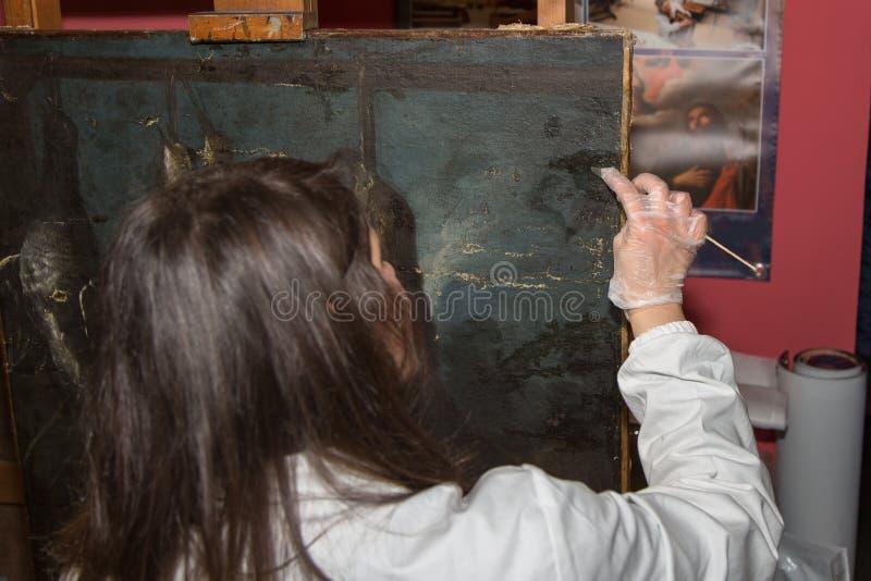 Um restaurador que esteja funcionando na restauração de uma pintura antiga imagem de stock
