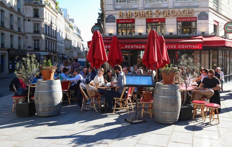 Um restaurante tradicional um St Georges do lugar do La em Paris no quadrado de StGeorges Parisians e os turistas apreciam o alim fotos de stock