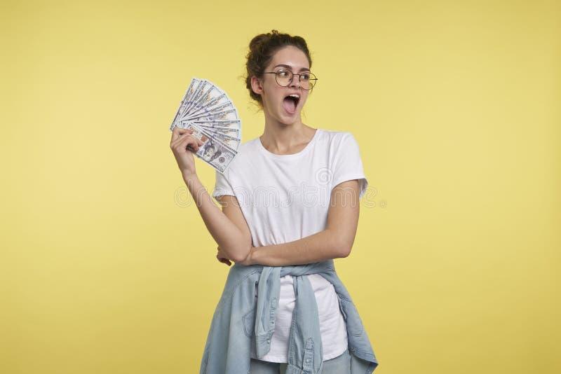 Um retrato da fêmea gritando feliz com desconta dentro a mão, ela olha à esquerda ao espaço da cópia foto de stock