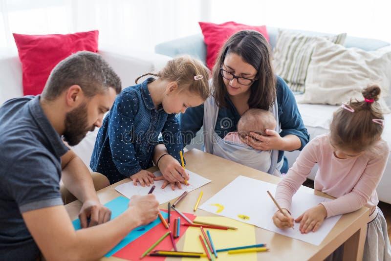 Um retrato da família nova com as crianças pequenas em torno da tabela dentro, tirando imagem de stock royalty free