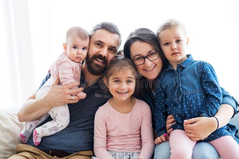Um retrato da família nova com as crianças pequenas que sentam-se dentro em um sofá fotos de stock royalty free