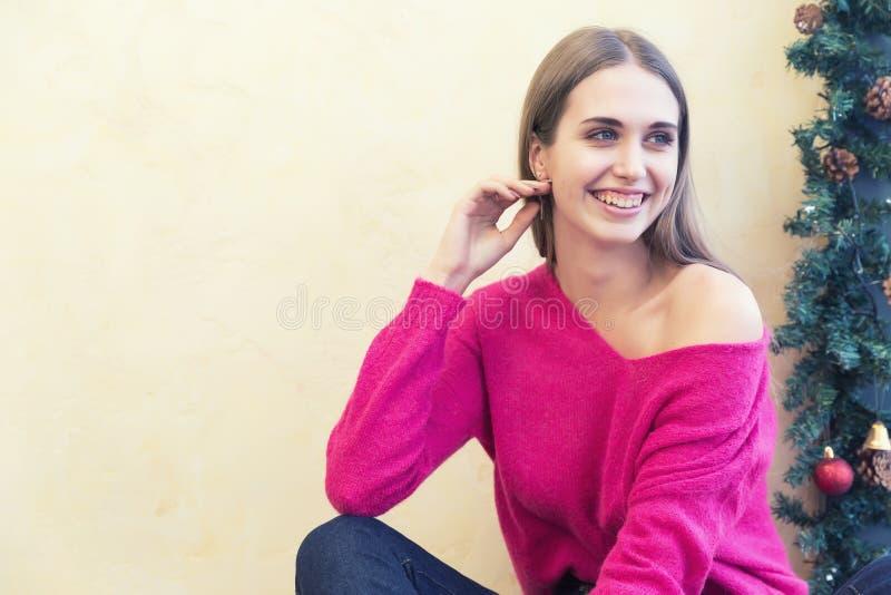 Um retrato da jovem mulher bonita no pulôver no fundo de luzes de Natal foto de stock royalty free