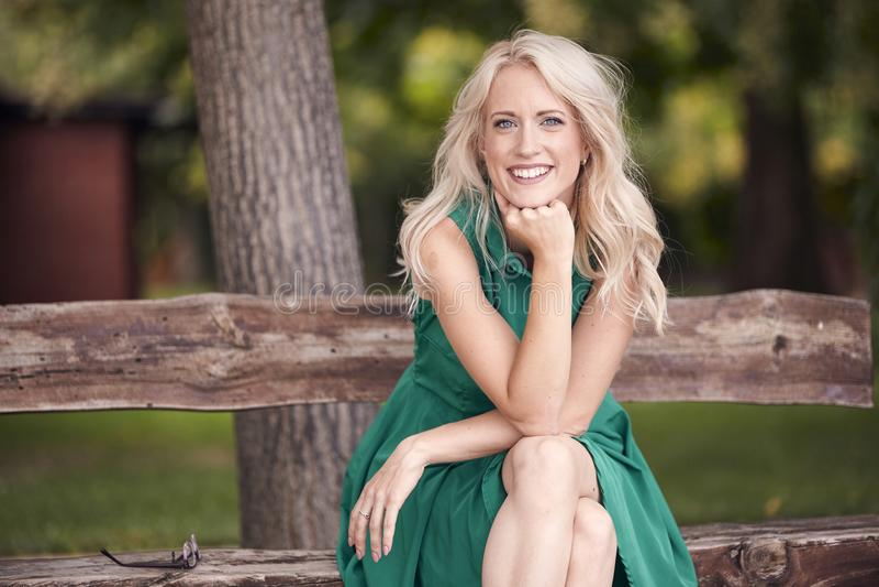 Um retrato da jovem mulher, sentando-se no banco de madeira, vestido do verde, 25 anos velho, sorriso feliz, olhando à câmera imagem de stock royalty free