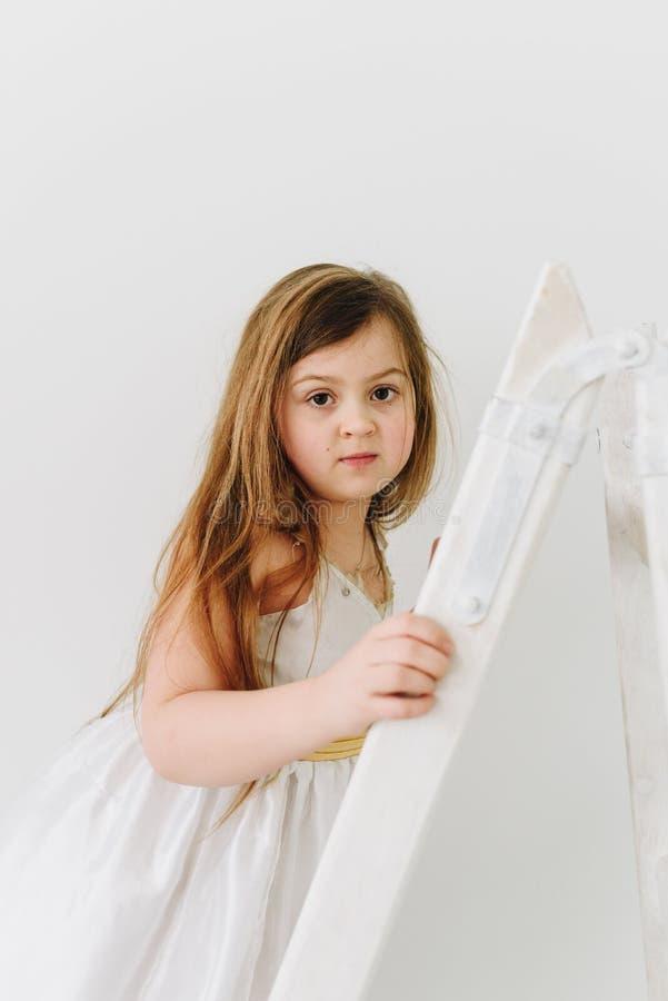Um retrato da menina bonito no vestido branco que inclina-se na escada foto de stock