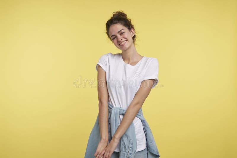 Um retrato da menina tímida bonita do estudante isolada sobre o fundo amarelo imagens de stock royalty free