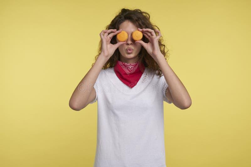 Um retrato da mulher italiana consideravelmente moreno e dos macarons sobre o fundo amarelo fotografia de stock royalty free