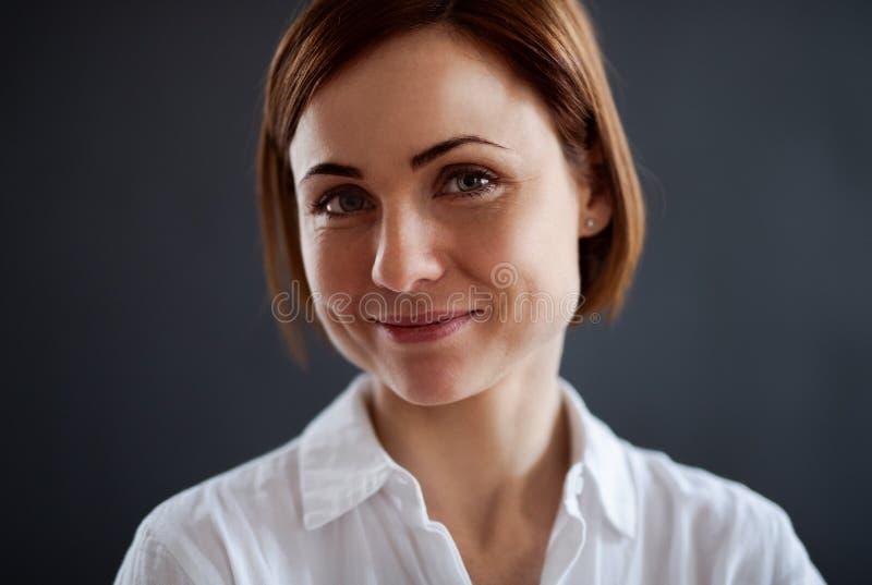 Um retrato da posição bonita nova da mulher contra o fundo escuro imagens de stock