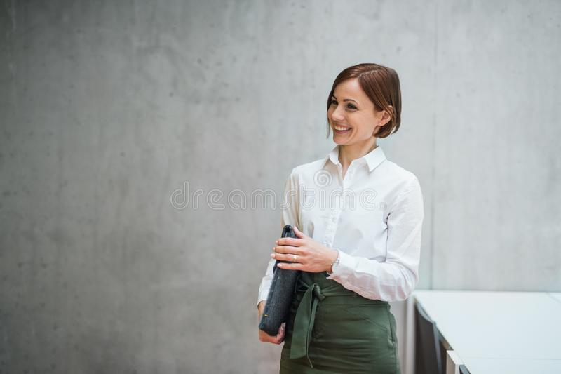 Um retrato da posição nova da mulher de negócios no escritório, guardando o saco do portátil foto de stock