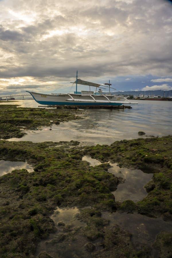 Um retrato de um barco durante o tempo do por do sol foto de stock royalty free