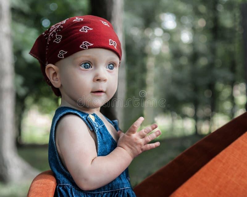 Um retrato de um bebê pequeno agradável com olhos azuis, vestindo um bandana vermelho e calças de ganga veste-se imagem de stock royalty free