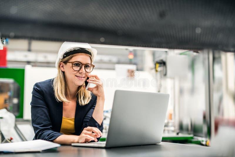 Um retrato de um coordenador industrial da mulher em uma fábrica usando o portátil e o smartphone imagens de stock
