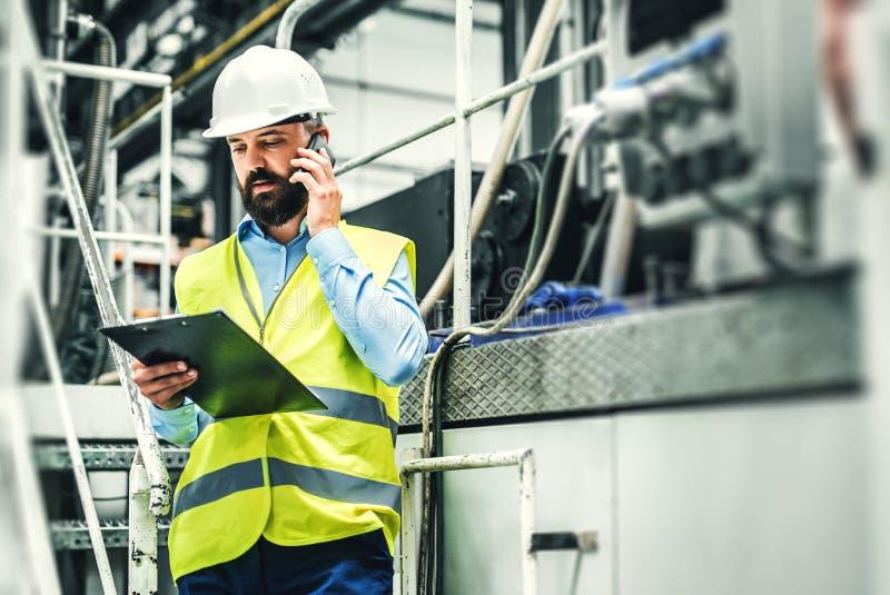 Um retrato de um coordenador industrial do homem com smartphone em uma fábrica, trabalhando foto de stock royalty free